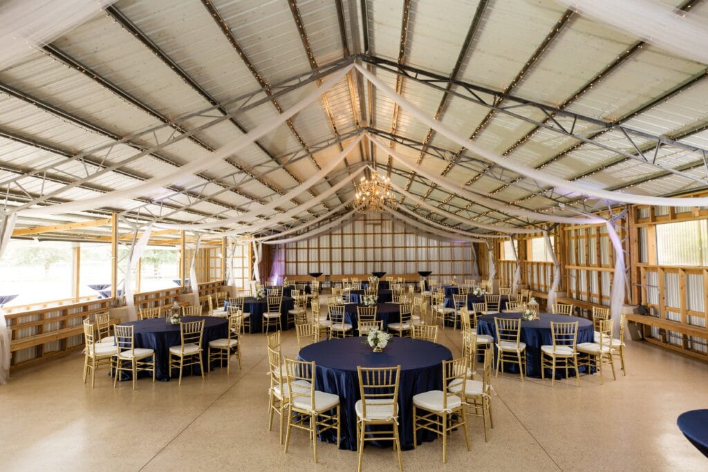 indoor modern barn wedding venue with blue tablecloths on round tables with white chairs and wood floor